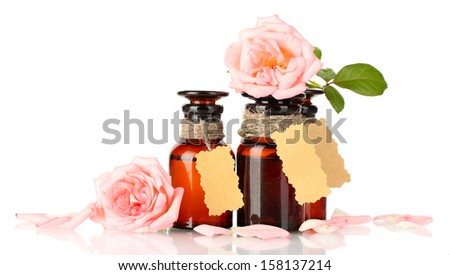bottles of oil and roses isolated on white - stock photo