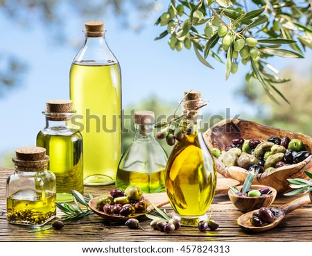 Bottles of olive oil on the old wooden table under olive tree. Blue sky on the background.