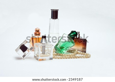 bottles of perfume with pearls isolated on white