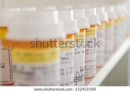 Bottles of pills arranged on shelf at drugstore - stock photo