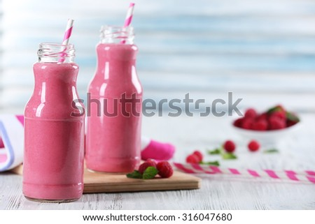 Bottles of raspberry milk shake with berries on wooden table close up - stock photo