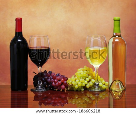 Bottles of Red and White Wine with Fresh Grapes. Glasses of Wine over Beige Background