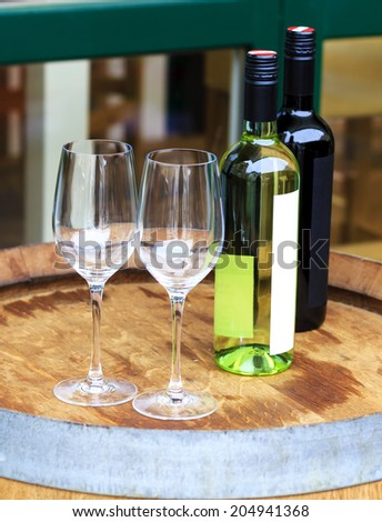 Bottles of red and white wine with two empty glasses on the barrel used as a table at Naschmarkt in Vienna, Austria - stock photo