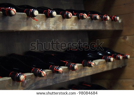 Bottles of red wine in rows in wine cellar - stock photo
