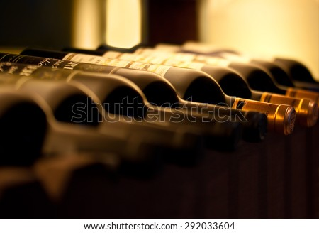 Bottles of red wine on a wooden shelf - stock photo