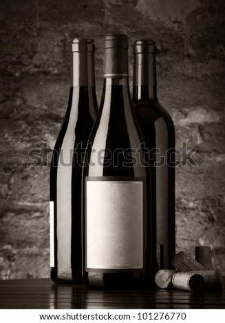 Bottles of red wine with corks and old brick wall background