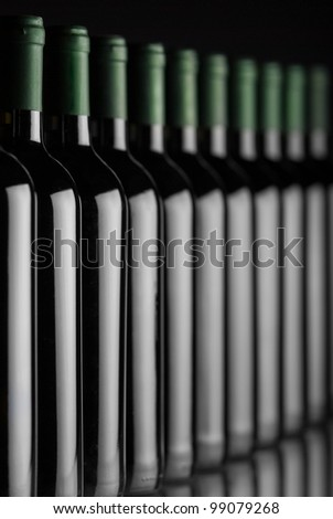 Bottles of white wine in a row with shallow depth of field - stock photo