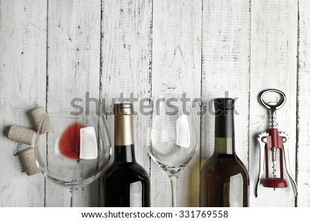 Bottles of wine, glass and corkscrew on wooden table,  black and white retro stylization - stock photo