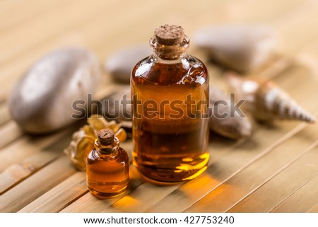 Bottles with aroma oil on bamboo background - stock photo