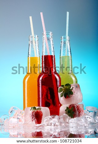 Bottles with colorful cocktails over blue background - stock photo