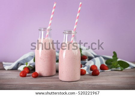 Bottles with delicious strawberry milkshake, napkin and berries on table and pink background