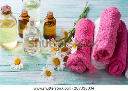 Bottles with essential aroma oil with chamomile and towels on  turquoise painted wooden background. Spa setting. Selective focus. - stock photo