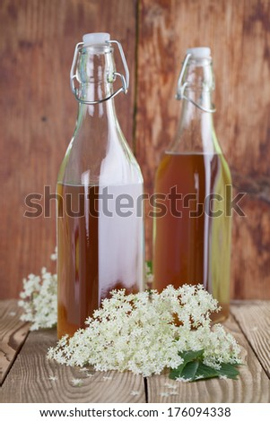Bottles with freshly made elderberry syrup, alternative medicine for cough, cold or flu. - stock photo