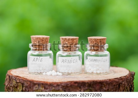 Bottles with homeopathy globules on green background - stock photo