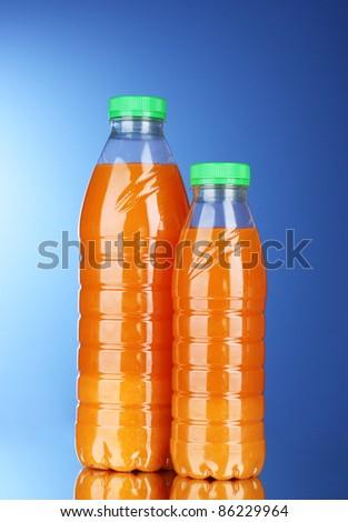 Bottles with juice on blue background - stock photo