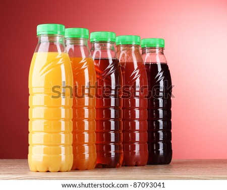 Bottles with juice on red background - stock photo
