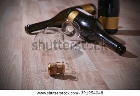 bottles with red wine stopper and an empty wine glass