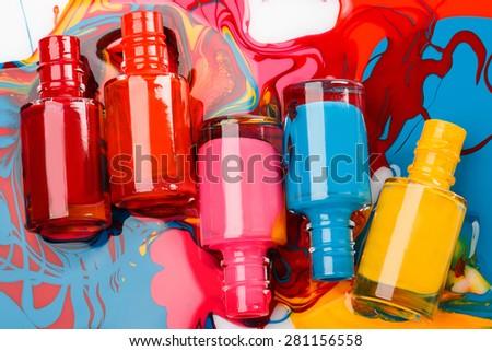 Bottles with spilled nail polish on white background - stock photo