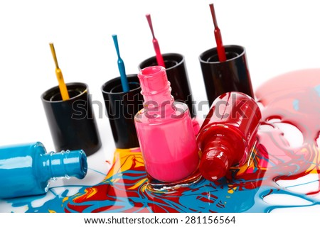 Bottles with spilled nail polish on white background - stock photo