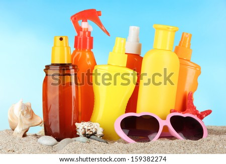 Bottles with suntan cream and sunglasses, on blue background - stock photo