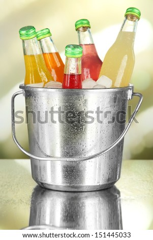 Bottles with tasty drinks in bucket with ice cubes, in bright background