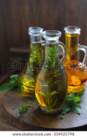 Bottles with various oil with herbs on a wood rustic table - stock photo