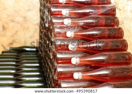 Bottles with wine in cellar, closeup