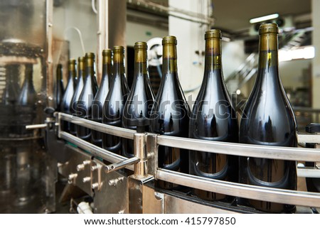 Bottling and sealing conveyor line at winery factory - stock photo