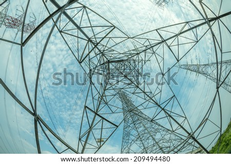 Bottom fisheye view of electric pylon with white cloud blue skies in the background. - stock photo