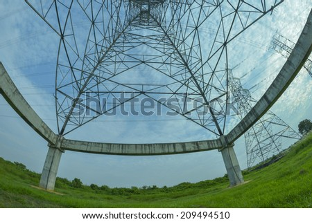 Bottom fisheye view of electric pylon with white cloud blue skies in the background.