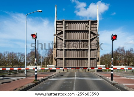 Bottom of the road surface of an open bridge. Red warning lights light up and the red and white boom barriers are closed. - stock photo