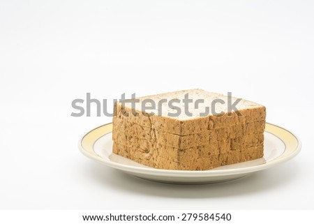 Bottom Right of Wholewheat Bread on Dish on White Background.