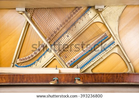 Bottom structure of an upright piano: pedals, metal frame with strings, bass and treble bridges. - stock photo