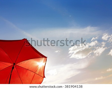 Bottom-up view of a red beach umbrella with a summertime sunny sky in background