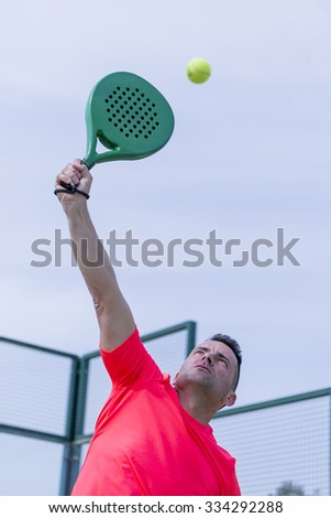 bottom view of a male paddle player smashing the ball in an outdoor court - focus on the chin