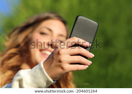 Bottom view of a woman hand texting on a smart phone with a green background                - stock photo