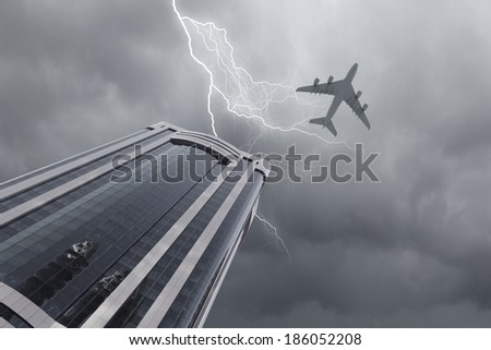 Bottom view of airplane flying above skyscraper in stormy sky