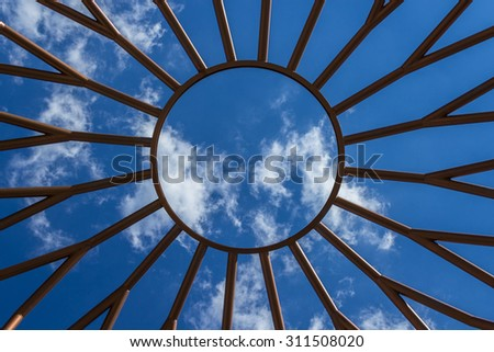 Bottom view of an iron structure, with blue sky in the background.