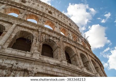Bottom view of ancient amphitheatre of Colosseum built by Vespasian and Titus in Rome, on cloudy blue sky background.