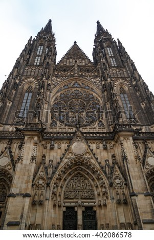 Bottom view of historical gothic St. Vitus Cathedral in old town of Prague, found in 1344, on cloudy blue sky background.