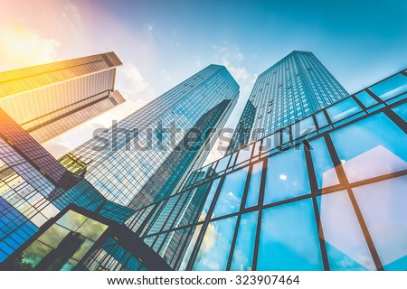 Bottom view of modern skyscrapers in business district in beautiful evening light at sunset with monochrome retro vintage Instagram style filter and lens flare light effect - stock photo