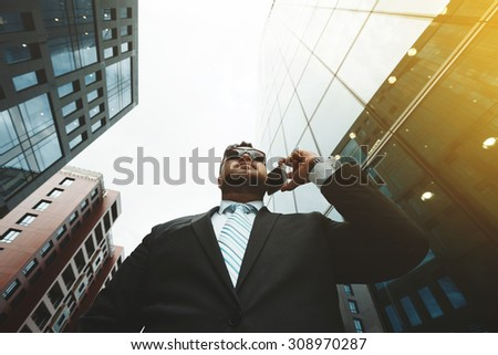 Bottom view portrait of successful business man talking on smart phone outside office. Attractive adult man in suit talking on phone and standing near his financial office  background, flare light