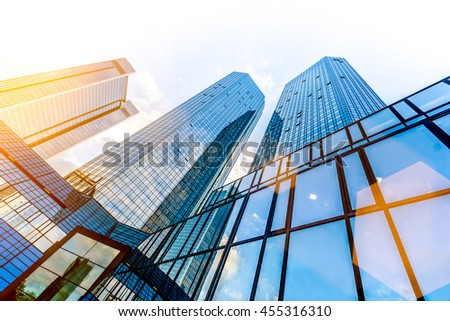 Bottom wide angle view of modern skyscrapers in business district in beautiful evening light at sunset with monochrome retro vintage Instagram style filter and lens flare sunlight effect - stock photo