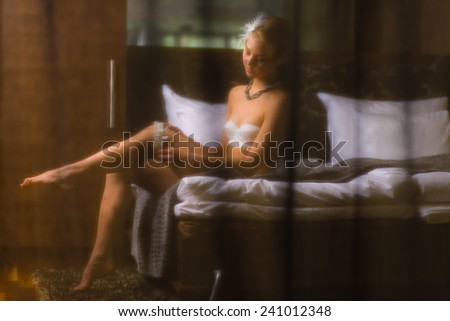 Boudoir, attractive young woman wearing lingerie and she sits on the bed - stock photo