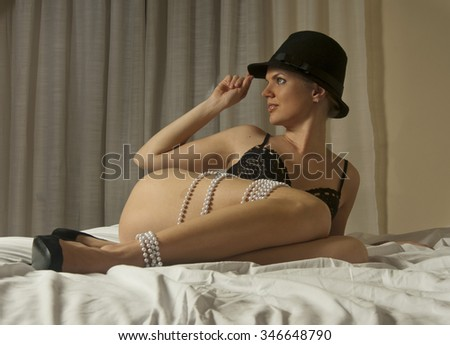 boudoir portrait of a beautiful girl with long sensual legs wearing black hat and black lingerie posing on the bed holding a hat and looking away - stock photo