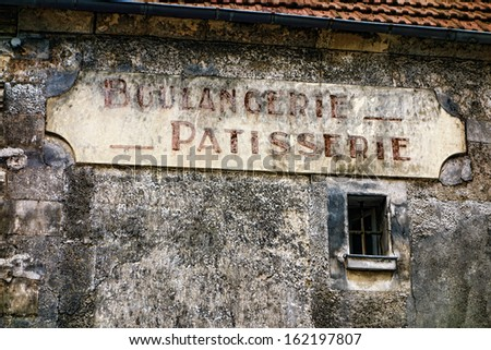 Boulangerie and patisserie French antique bakery and pastry shop old and distressed store sign hanging on a derelict grunge wall of an ancient and damaged building in a small rural town in France