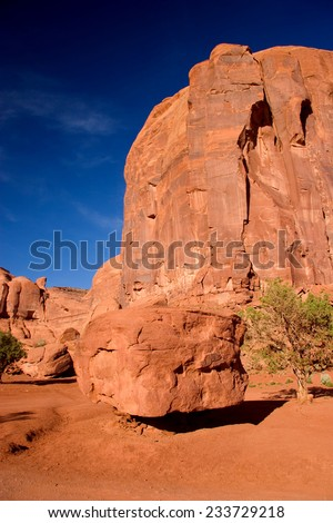Boulder balancing on sand pile. Monument Valley in the Navajo Tribal Park, northeastern Arizona, USA - stock photo