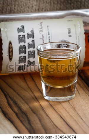 Boulder City Nevada - December 25 : Shot glass with a bottle of Rebel Yell bourbon in the background, December 25 2014 in Boulder City, Nevada - stock photo