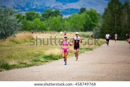 Boulder, Colorado, USA - July 24, 2016: Maria Poblete runs to a win at Tri Boulder as she passes other runners along the trails at Boulder Reservoir.