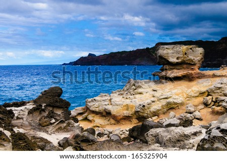 Boulder on a edge of cliff overlooking the Pacific Ocean, Maui, Hawaii, USA - stock photo